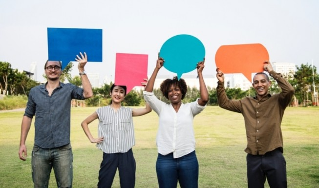 people in a park holding up speech bubbles