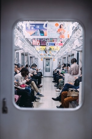 people on the train in japan staring at their mobile phones